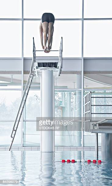 Man jumping from a highboard in an indoor swimming pool