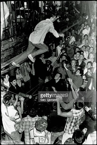 Man jumping from balcony onto the crowd during a punk show at The Starwood