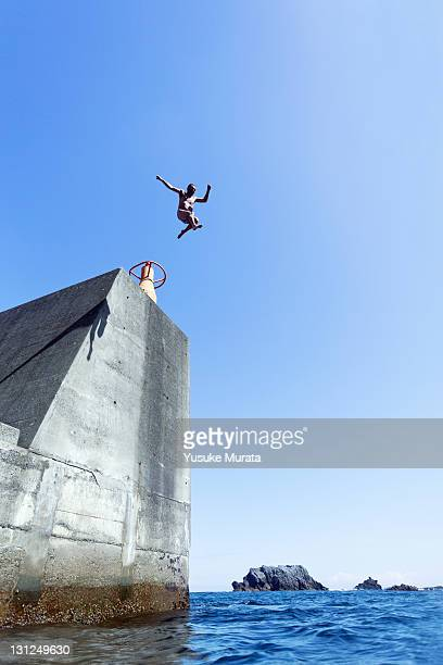man jumping from breakwater
