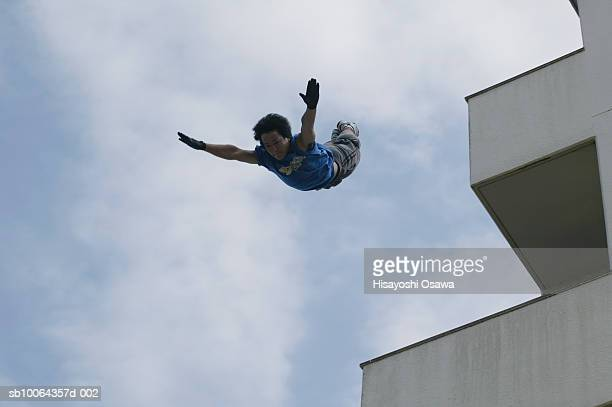 Man jumping from building, low angle view
