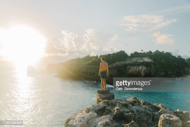 uomo che salta dalla scogliera nella laguna blu su nusa ceningan - scogliera foto e immagini stock