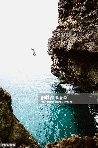 man jumping from cliff into sea - falaise photos et images de collection