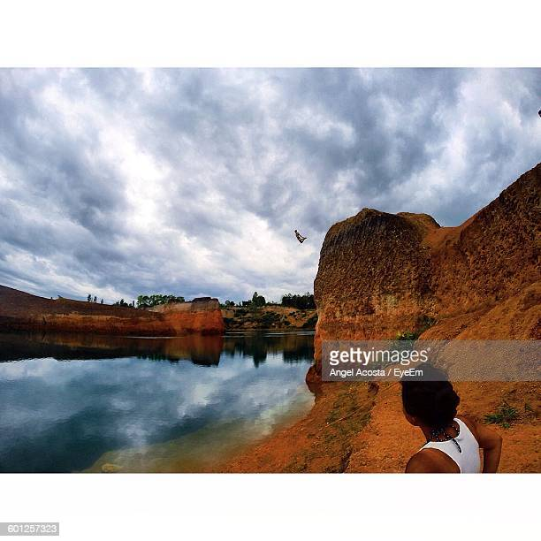 Man Jumping From Cliff Over Lake Against Sky