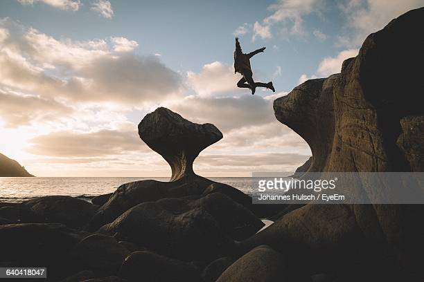 Man Jumping From Cliff Over Rocks Against Sky