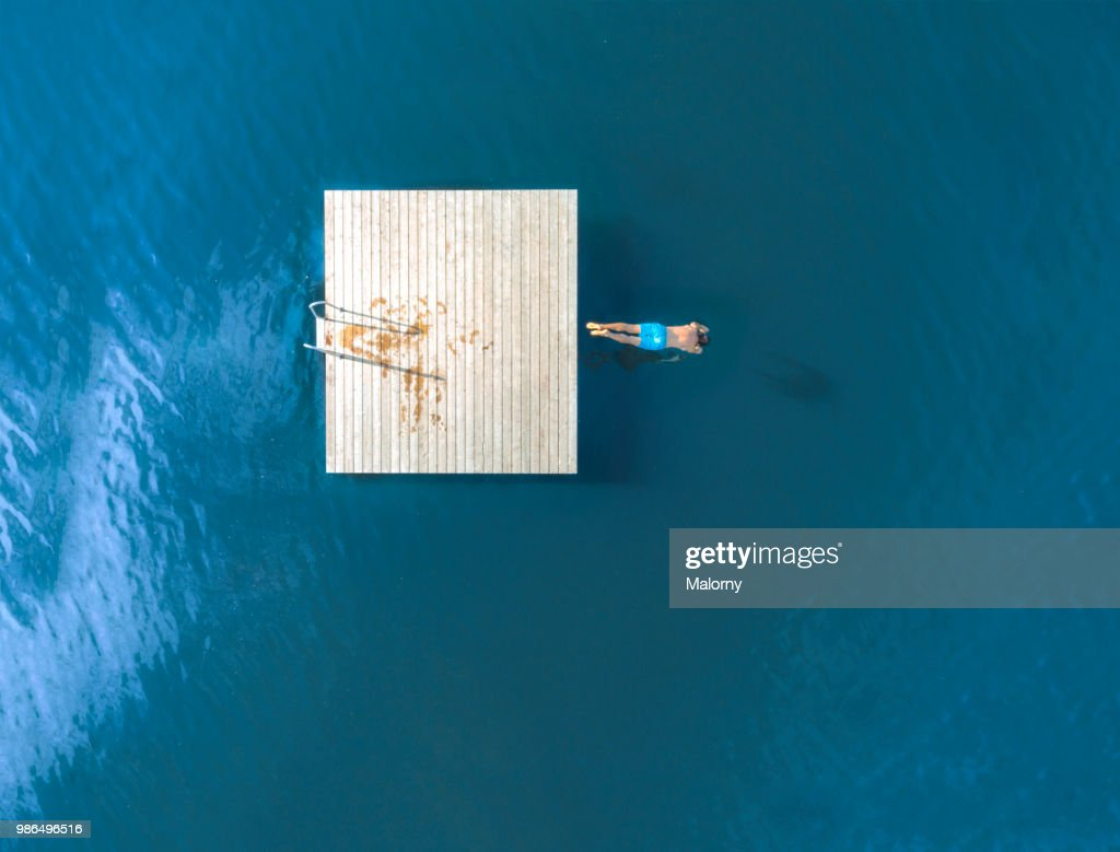 Man jumping from floating island into blue lake. Directly above, aerial view. Drone view. : Stock-Foto