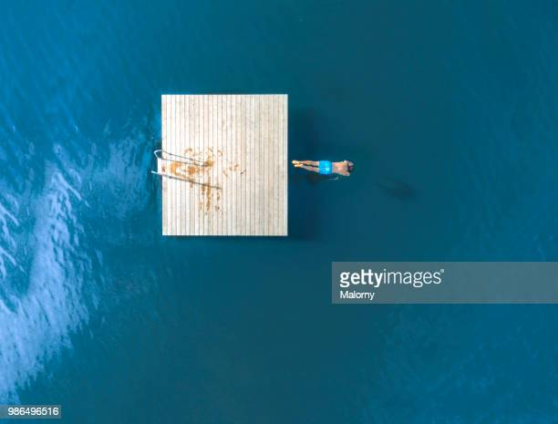 Man jumping from floating island into blue lake. Directly above, aerial view. Drone view.