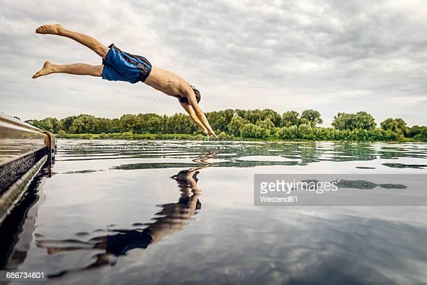man jumping from jetty into water - calzoncini da bagno foto e immagini stock