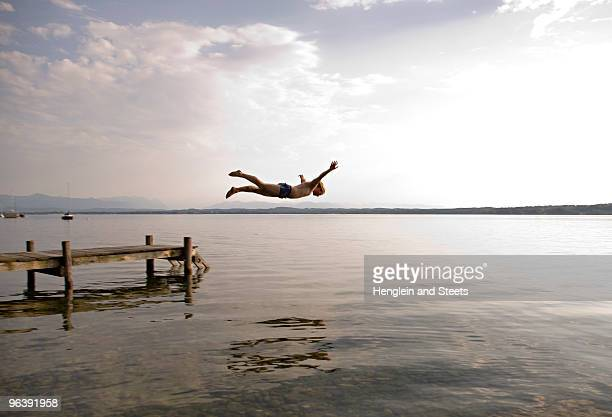 man jumping from pier - pier stock pictures, royalty-free photos & images