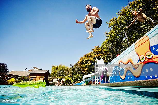 Man jumping from wall into outdoor pool