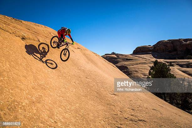 man jumping his mountain bike on slickrock.  - exhilaration stock pictures, royalty-free photos & images