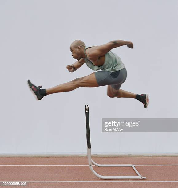 man jumping hurdle, side view - hurdling stock photos and pictures