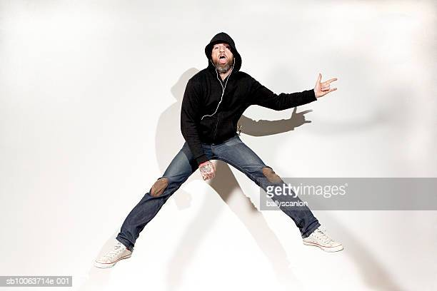 Man jumping in air while playing air guitar, portrait