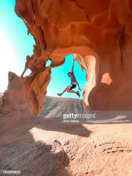 man jumping in front beautiful rock formations with natural arch in fuerteventura island. spain. el arco de las peñitas en fuerteventura uno de los sitios mas famosos de instagram. - 放浪願望 ストックフォトと画像
