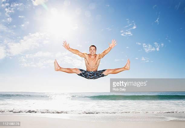 Homme sautant en l'air sur la plage