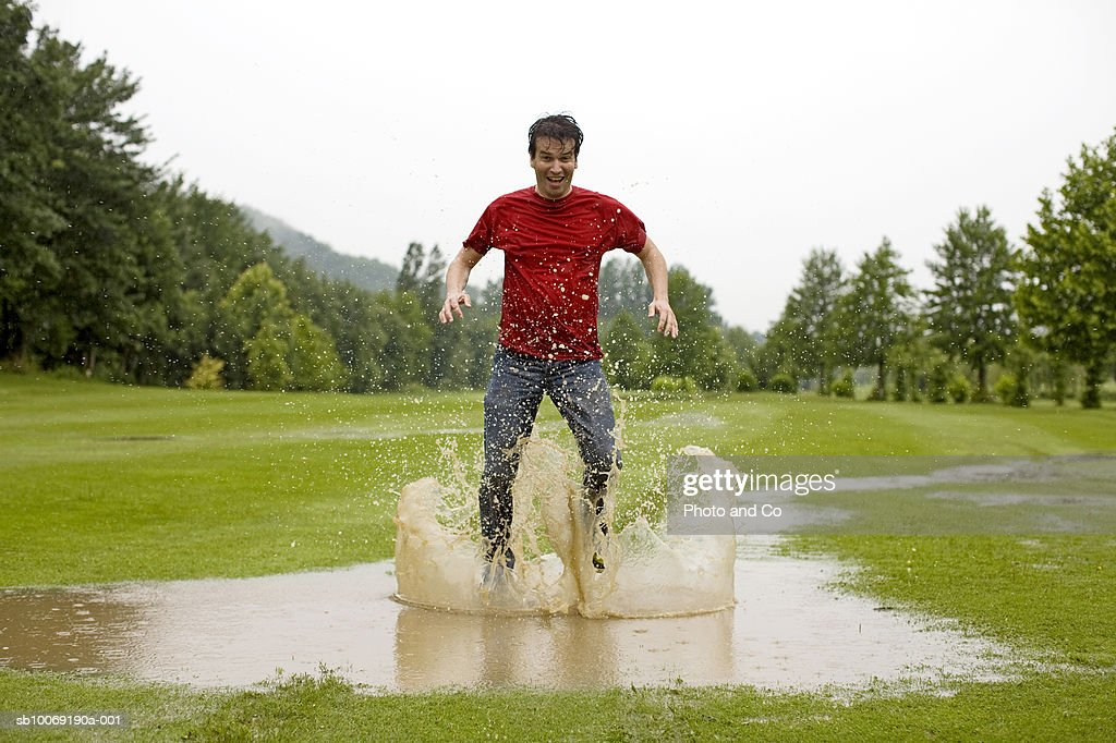 Man jumping in puddle on golf course : Stockfoto