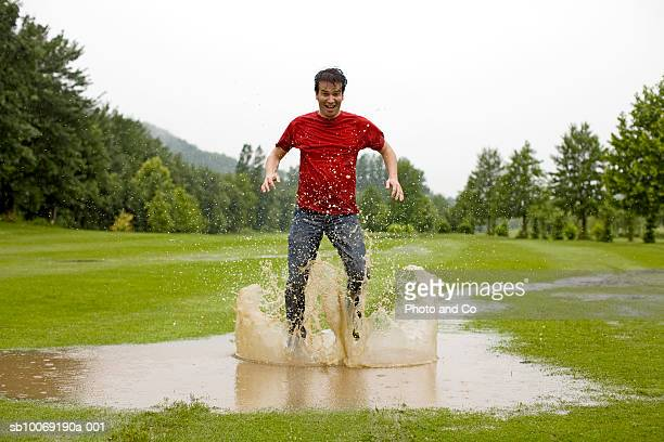 Man jumping in puddle on golf course