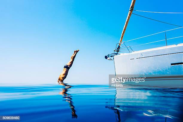 man jumping in sea from sailboat - water sport stock photos and pictures