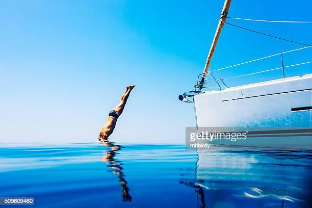 Homme de sauter dans la mer depuis un bateau à voile