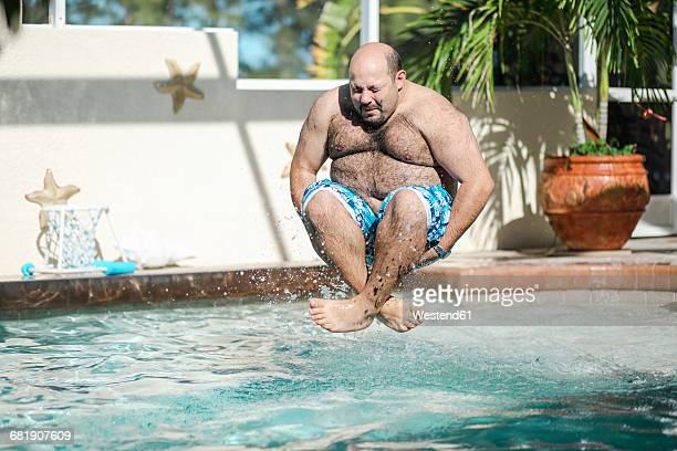 man jumping in swimming pool - naughty america stock pictures, royalty-free photos & images
