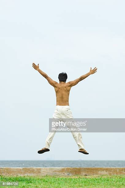 Man jumping in the air at the beach, arms raised, rear view