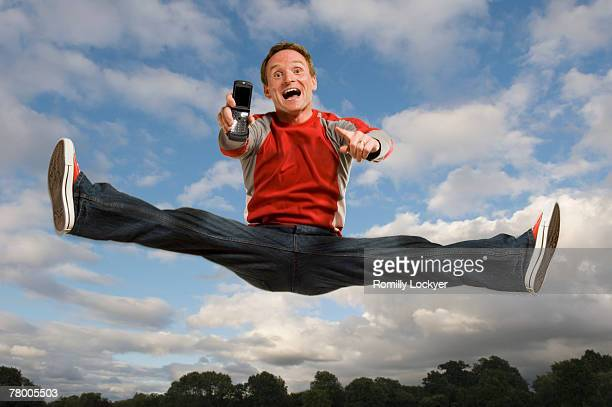 Man jumping in the air holding his cell phone