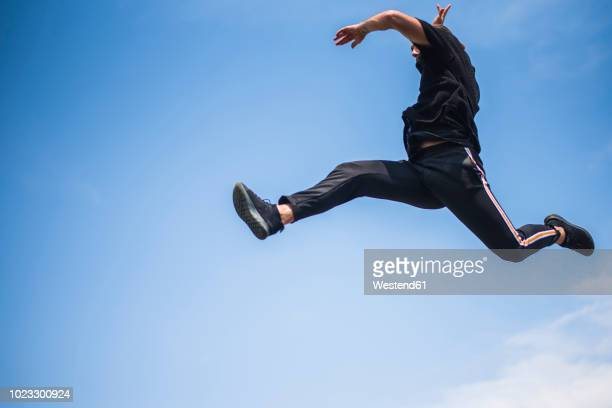 man jumping in the air - acrobatic activity stock photos and pictures