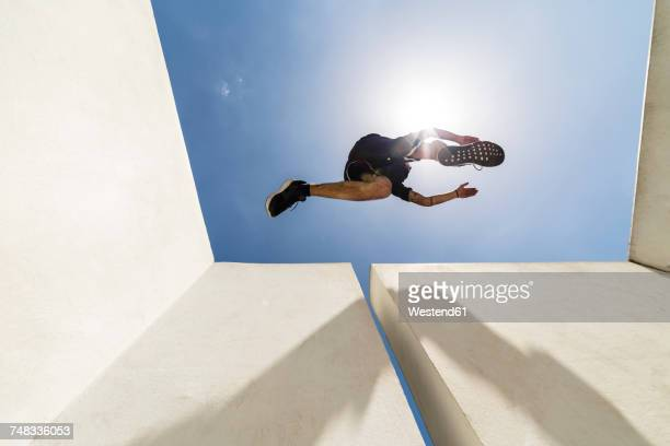 man jumping in the city during a parkour session - vista de ángulo bajo fotografías e imágenes de stock