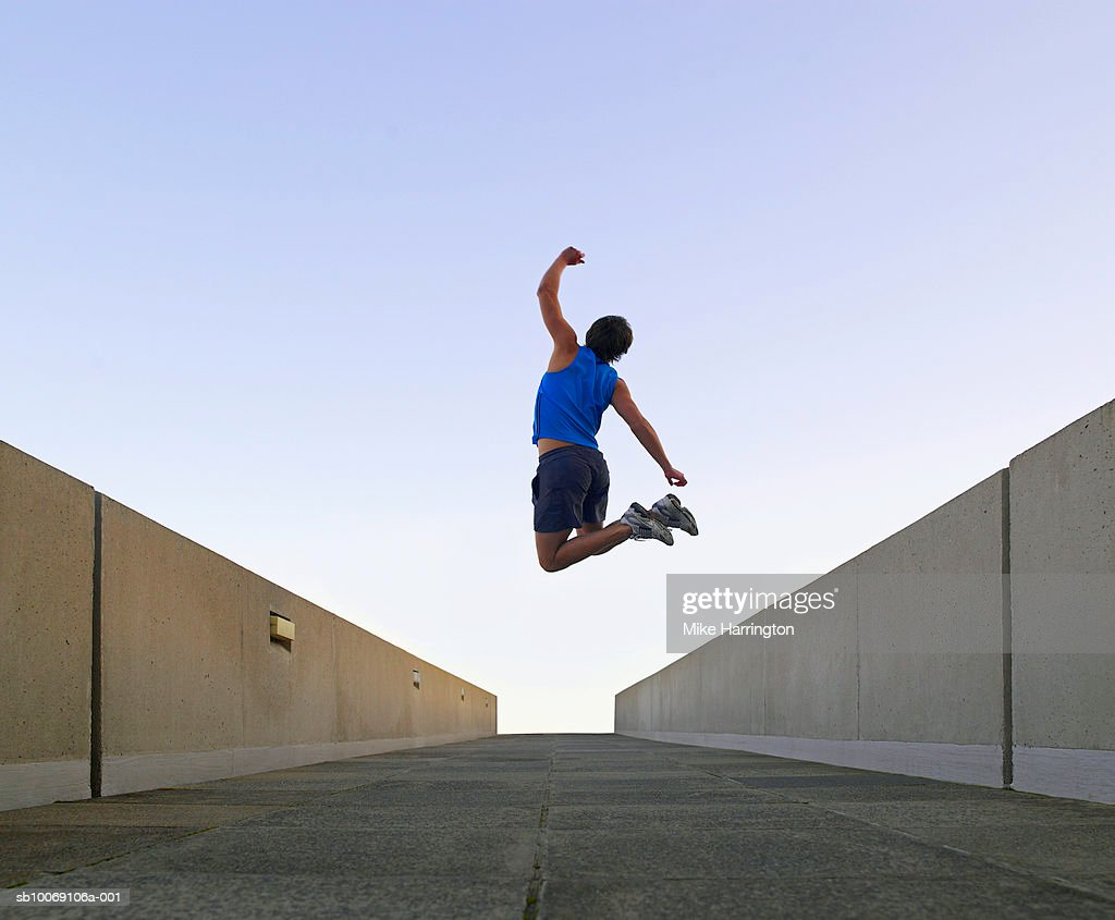 Man jumping in urban setting, rear view : Stockfoto