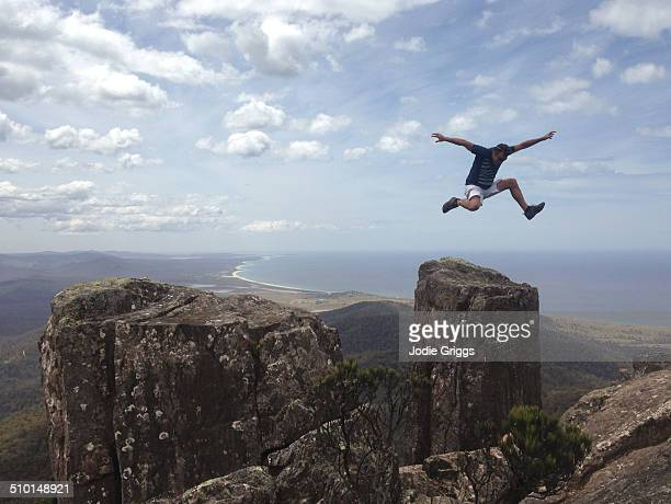 Man jumping into air on mountain peak near coast