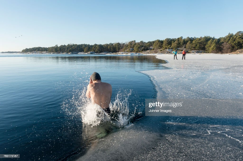 Man jumping into freezing cold water : Stock-Foto