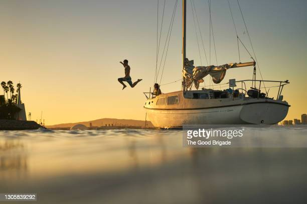 man jumping into ocean from deck of sailboat at sunset - pacific ocean stock pictures, royalty-free photos & images