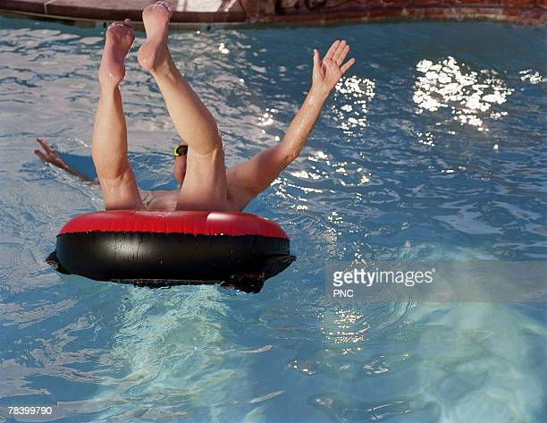 Man jumping into pool in innertube