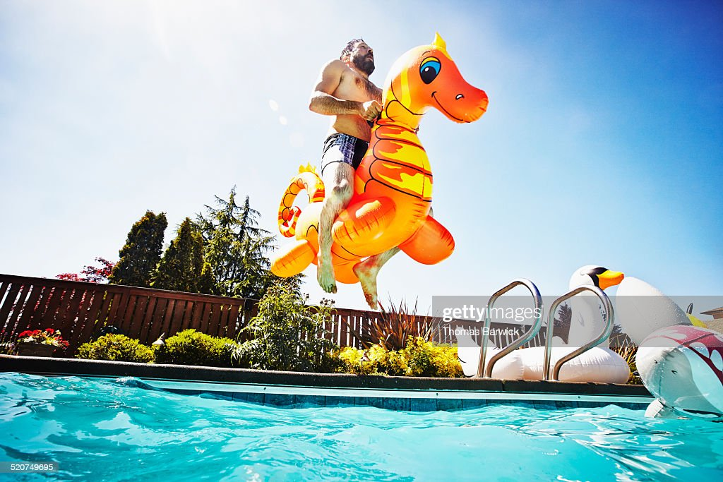 Man jumping into pool with inflatable pool toy : Stock Photo