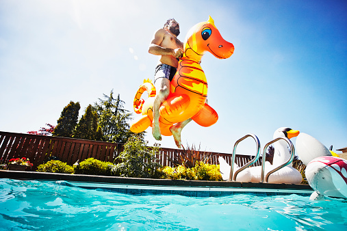 Man jumping into pool with inflatable pool toy - gettyimageskorea