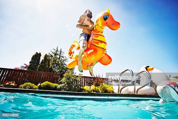 man jumping into pool with inflatable pool toy - insouciance photos et images de collection
