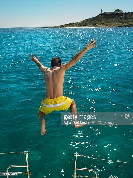 Man jumping into sea from boat, rear view