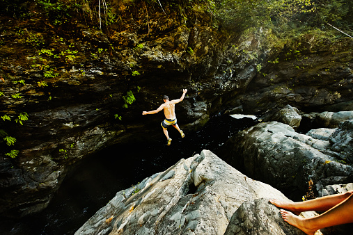 Man jumping into swimming hole arms outstretched - gettyimageskorea