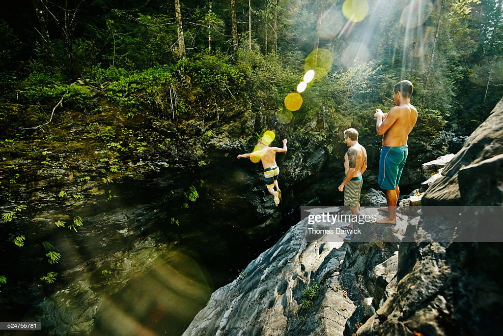 Man jumping into swimming hole while friends watch : Stock Photo