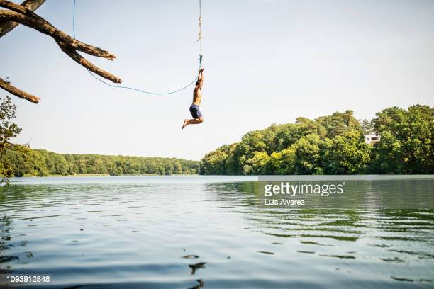 man jumping into the lake from the swinging rope - freizeit stock-fotos und bilder