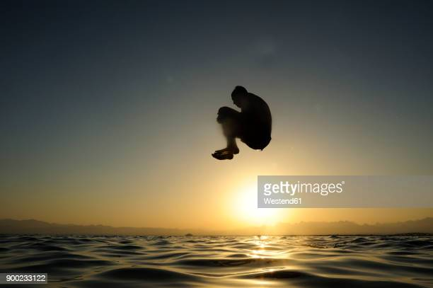 man jumping into the sea at sunset - cannon stock pictures, royalty-free photos & images