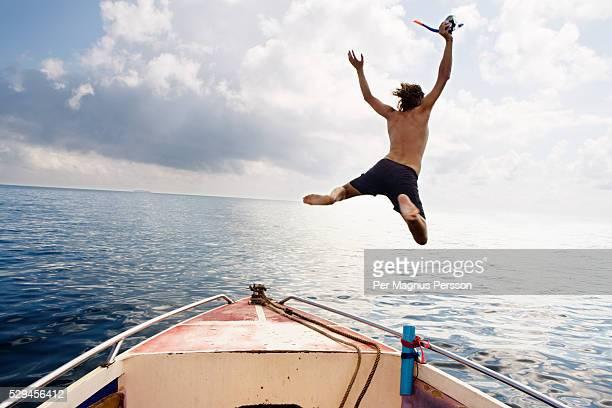 a man jumping into the sea thailand - calzoncini da bagno foto e immagini stock