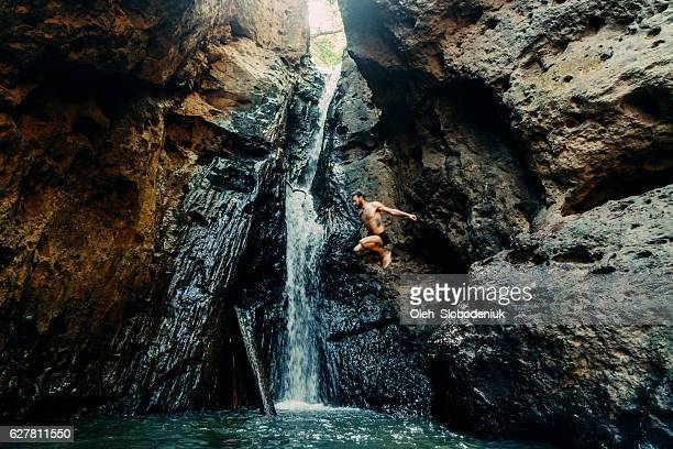 man jumping into tropical waterfall - waterfall stock pictures, royalty-free photos & images