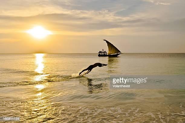 Man jumping into water in Zanzibar at sunset