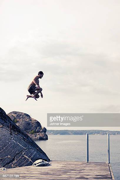 man jumping into water - västra götalands län stockfoto's en -beelden