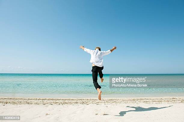 man jumping midair on beach, rear view - islas baleares fotografías e imágenes de stock