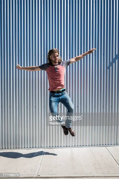 Man jumping mid-air on pavement