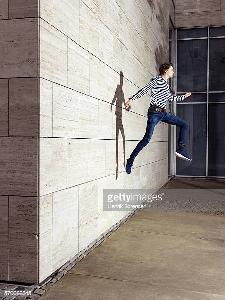 man jumping off a wall - down blouse stock pictures, royalty-free photos & images