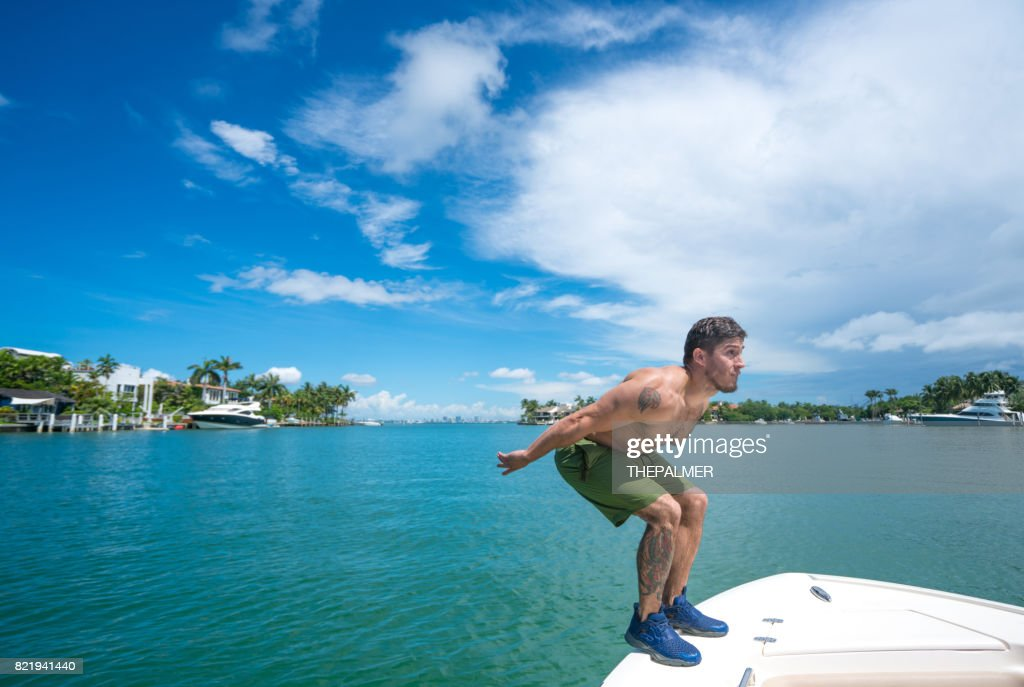Man jumping off boat : Stock Photo