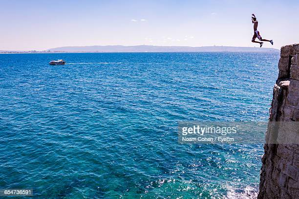 man jumping off cliff into sea - taking the plunge stock photos and pictures