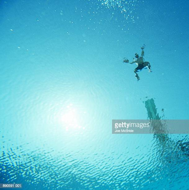 Man jumping off diving board into water, underwater view